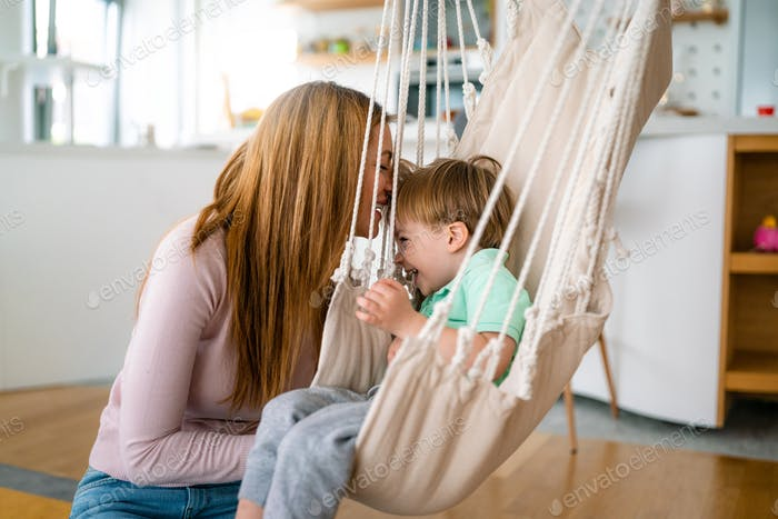 Family, childhood, single parent concept. Happy woman and little son having fun together at home