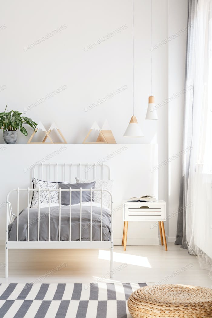 Pouf on patterned carpet near grey bed in white kid's bedroom in