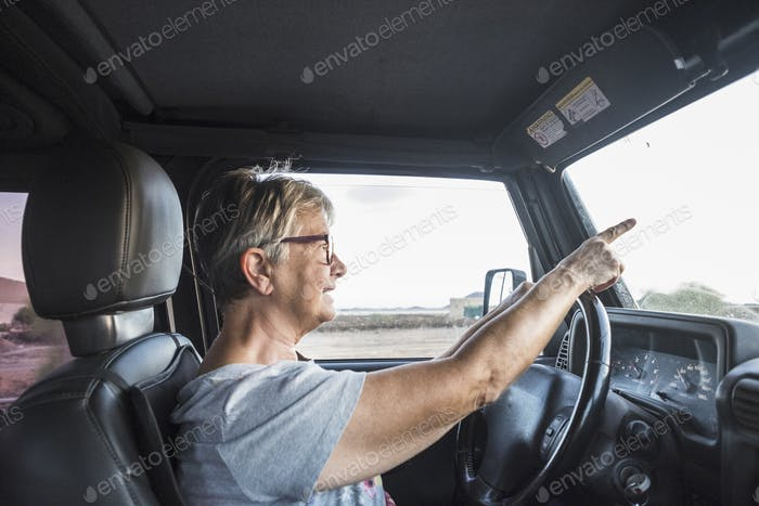 adult senior woman drive the car and pay attention to the traffic.