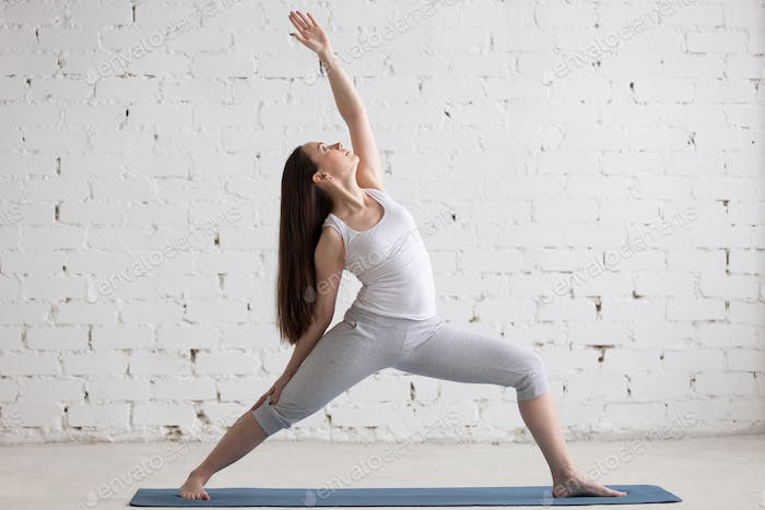 Side view portrait of happy woman doing Reverse Warrior Pose
