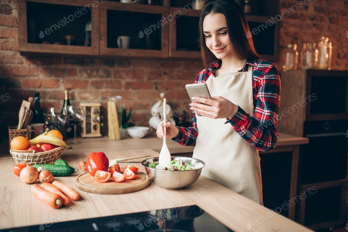 Woman use phone while cooking vegetable salad