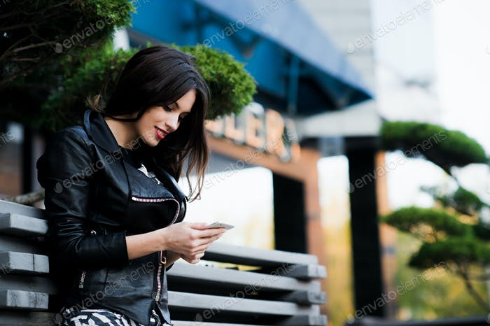 Young beauty woman writing message on cell phone in a street cafe. Looking down