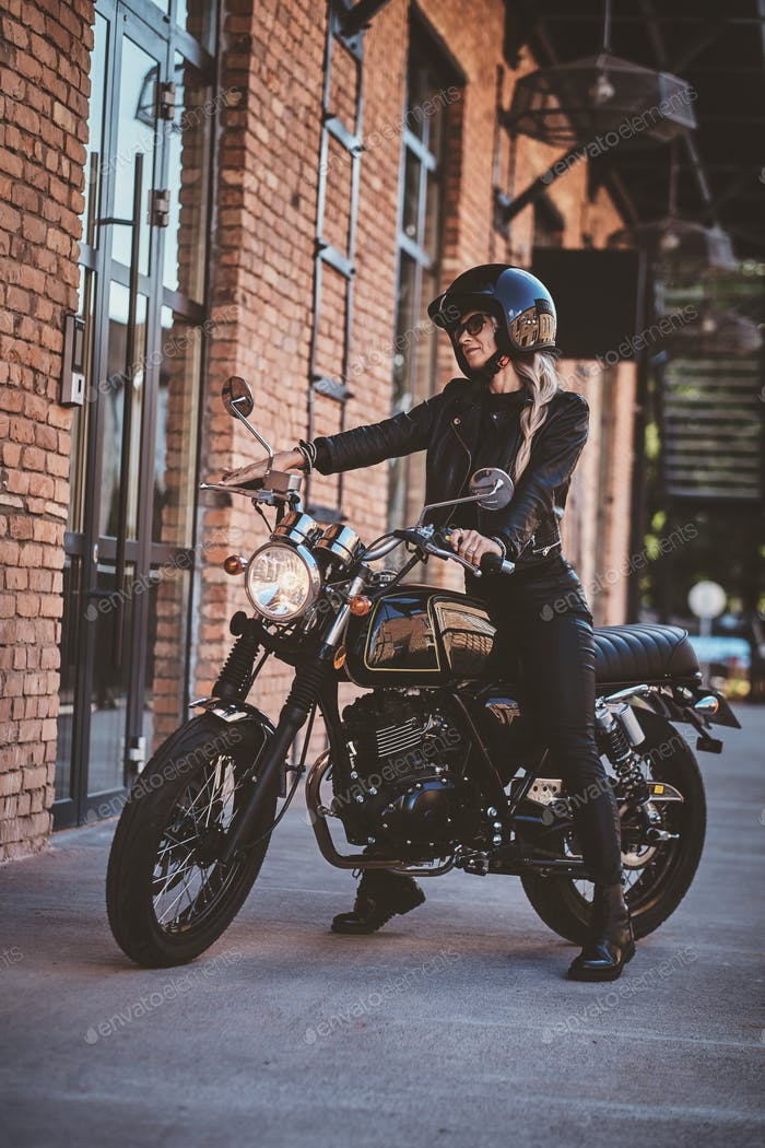 Handsome female biker is posing for photographer with her motorbike