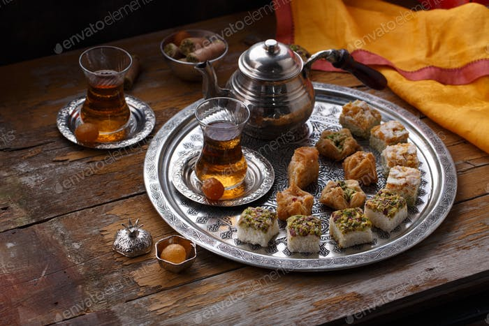 Turkish tea with turkish delights on copper plate, copy space