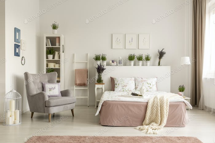 Real photo of a feminine bedroom interior with a comfy armchair,