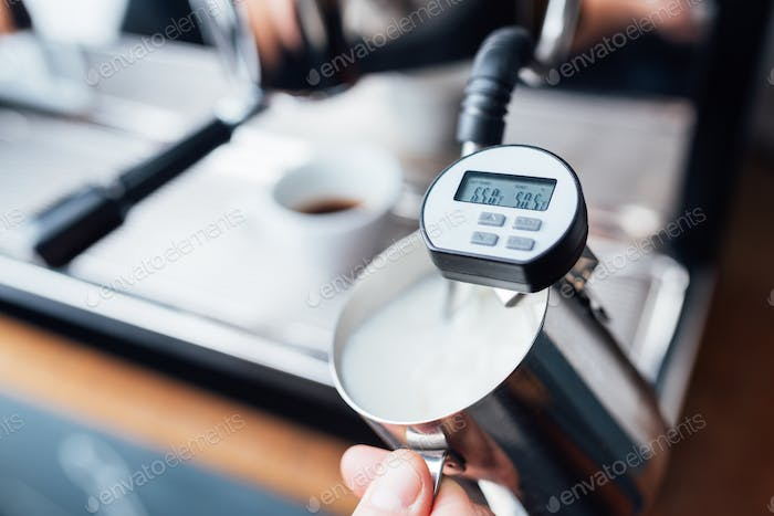measuring the temperature of milk foaming with steam under pressure from a coffee machine
