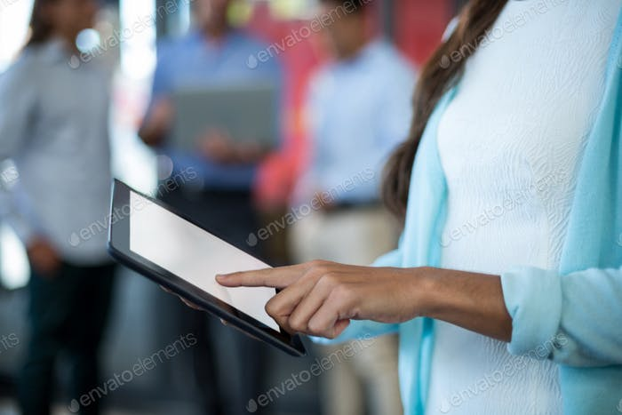 Mid section of businesswoman using digital tablet