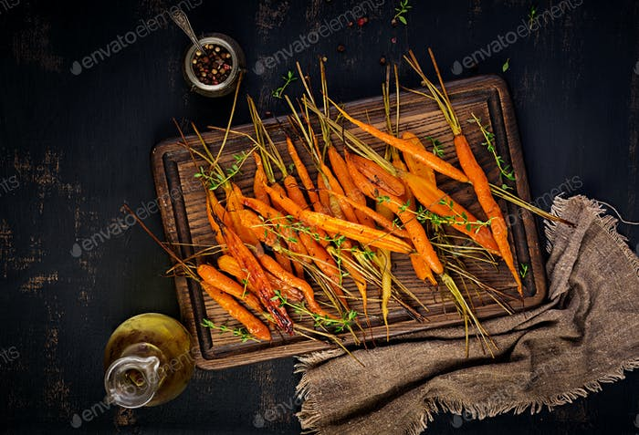 Baked organic carrots with thyme, honey and lemon. Organic vegan food. Top view