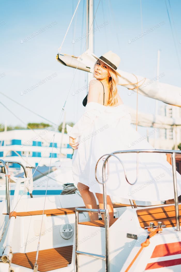 Beautiful sensitive blonde young woman in short and straw hats on  yacht at pier