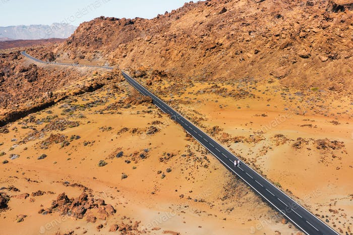 A couple in love walks along the road in the crater of the Teide volcano.Mars is the desert