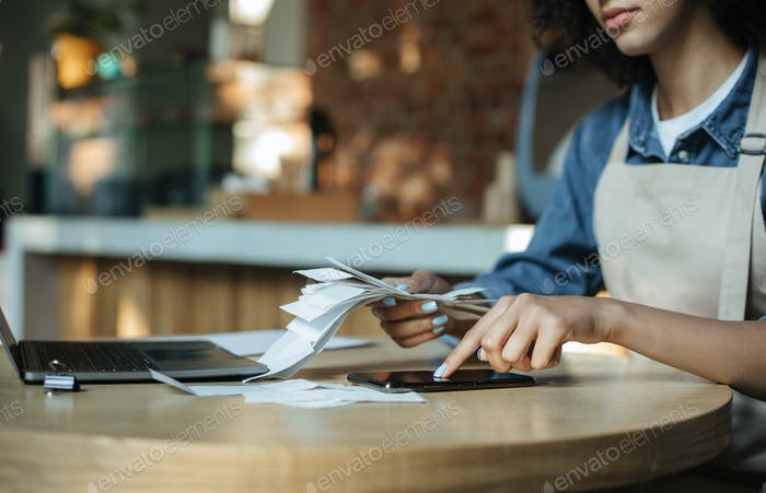 Busy african american lady owner in apron works with financial bills