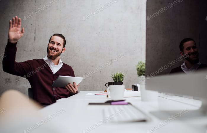 A young businessman with tablet in office, greeting somebody.