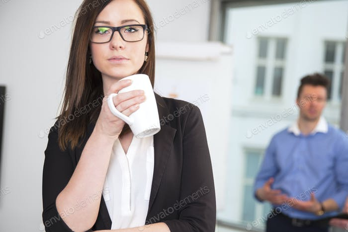 Businesswoman Holding Coffee Mug While Colleague Standing In Bac