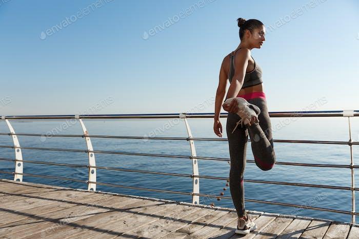 Rear view of sportswoman stretching her leg before running along seaside