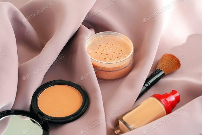 Base de maquillaje y polvo facial sobre paño rosa sedoso