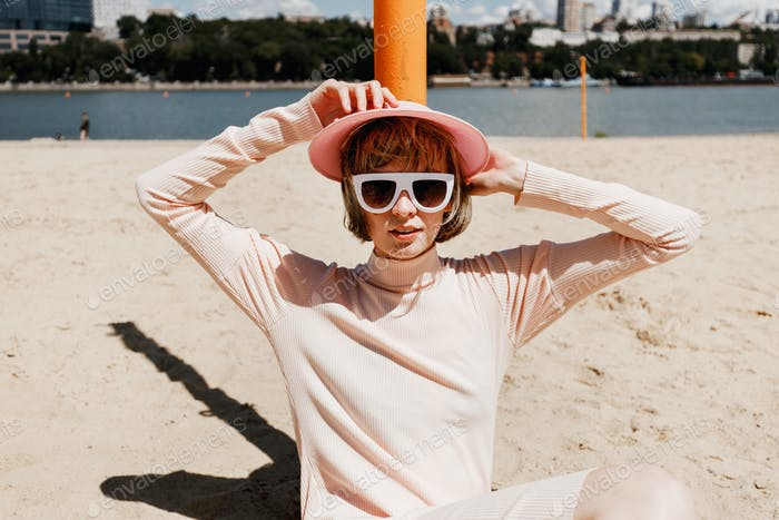 Stylish girl in white sunglasses, a gently pink dress and pink visor sits on a sandy beach leaning
