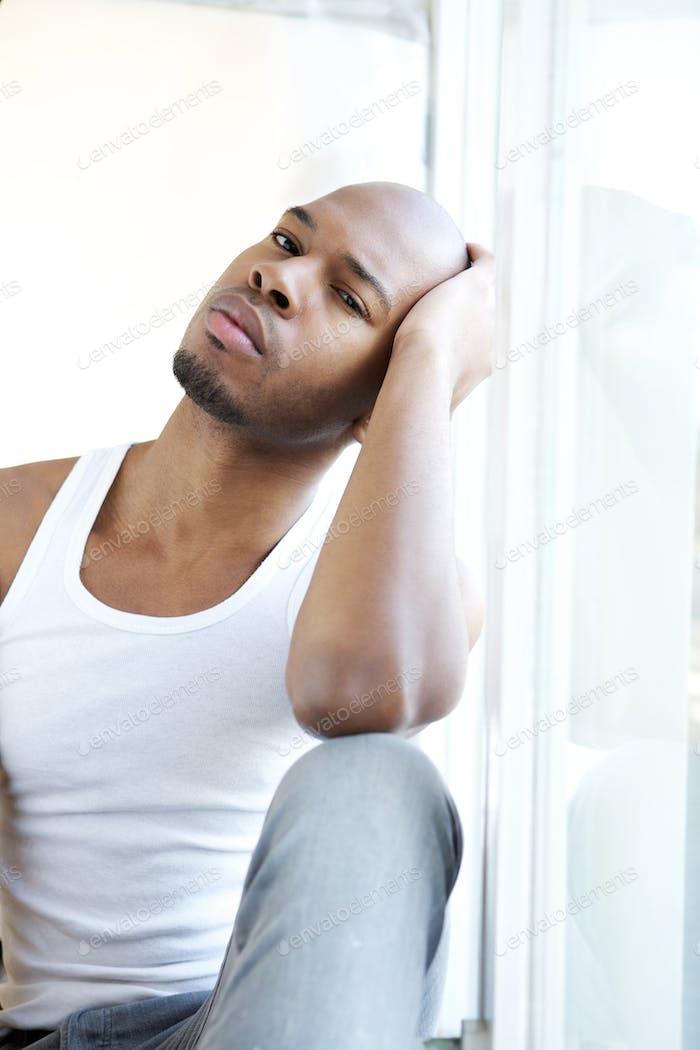 Porträt eines jungen Mannes entspannen durch Fenster