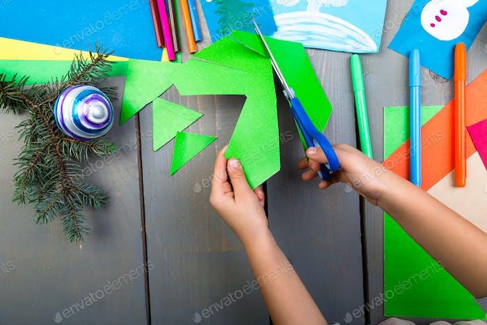 Kinderhände machen handgefertigte Weihnachtsspielzeuge aus Pappe. Kinder-DIY-Konzept
