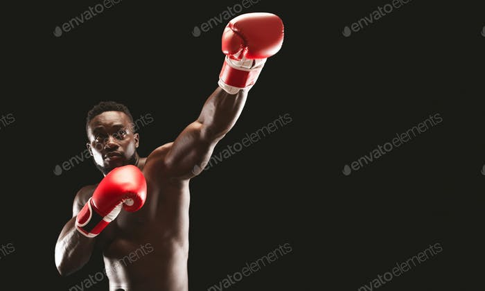 MMA african boxer showing big punch over black studio background