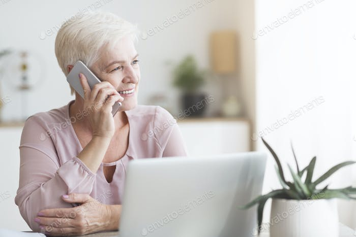 Positive old woman talking by phone with clients