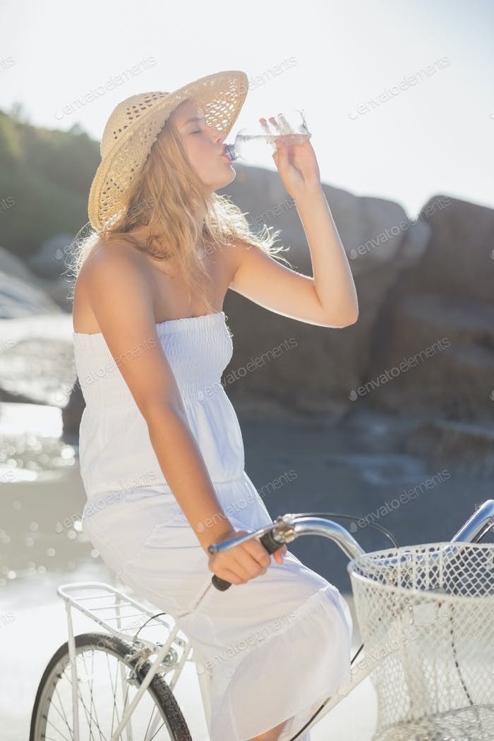Beautiful blonde in white sundress on bike drinking water at the beach on a sunny day