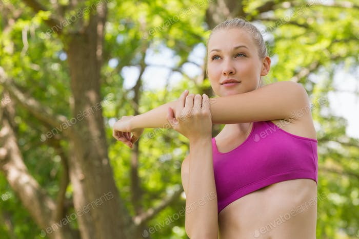 Healthy and beautiful young woman in sports bra stretching hand against trees in the park