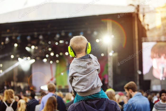 Boy with headphones being carried on shoulders during festival