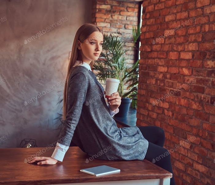 A young slim sexy girl in a gray dress holds a cup of coffee sit