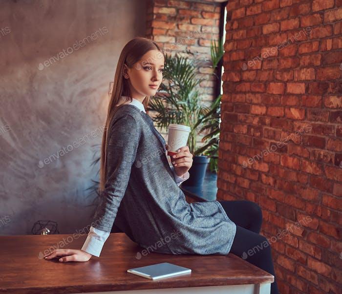 Молодая стройная сексуальная девушка в сером платье держит чашку кофе сидеть
