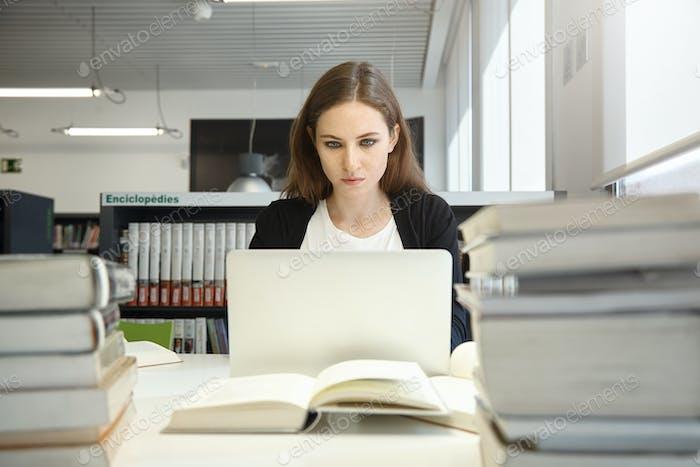 Студентка колледжа с длинными волосами, изучающая в университетской библиотеке или учебной комнате, набрав на generi