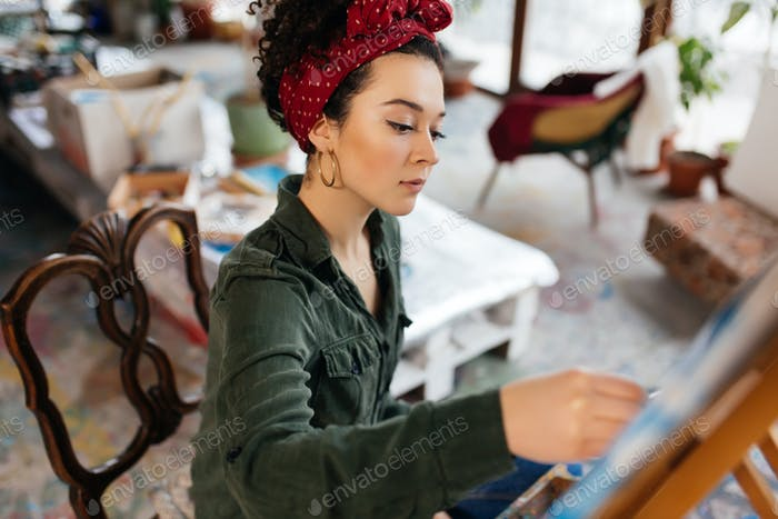 Young serious woman with dark curly hair sitting on chair though