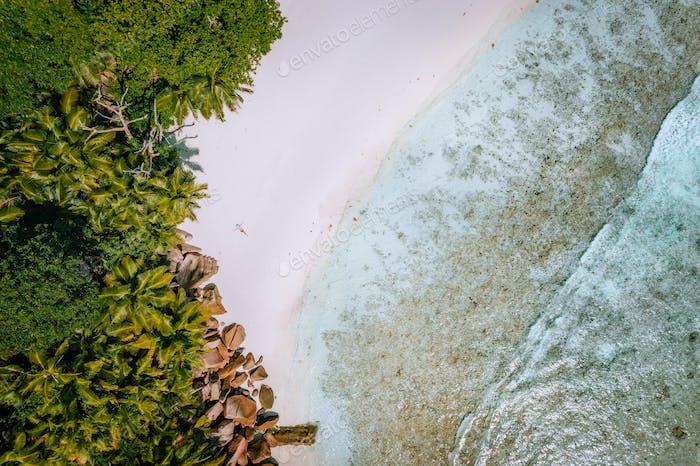 Von  oben nach unten Luftbild einer jungen Frau am paradiesischen tropischen Strand. Kristallklare Lagune, Sommer