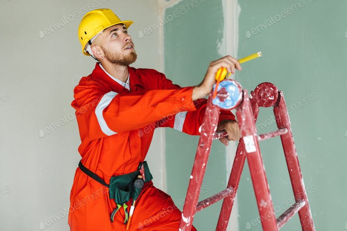 Young builder in orange work clothes and yellow hardhat standing