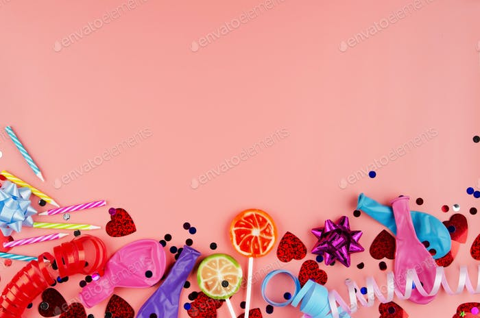Festive anniversary preparation tinsel with baloons and candles on pink background. Space for text