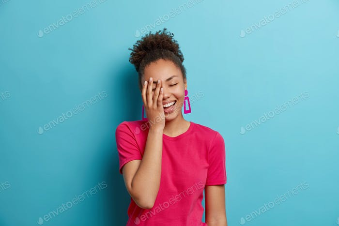 Portrait of attractive curly haired woman laughs out loudly makes face palm and smiles broadly dress