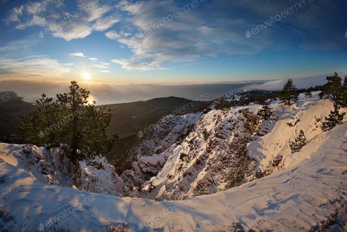 Bäume im Schnee gegen den blauen Himmel mit Wolken und Sonne