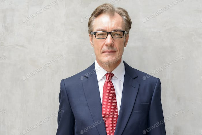Face of handsome mature businessman with eyeglasses against concrete wall