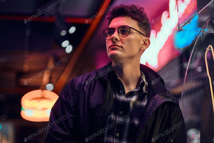 Young man fashionably dressed standing in the street at night. Illuminated signboards, neon, lights
