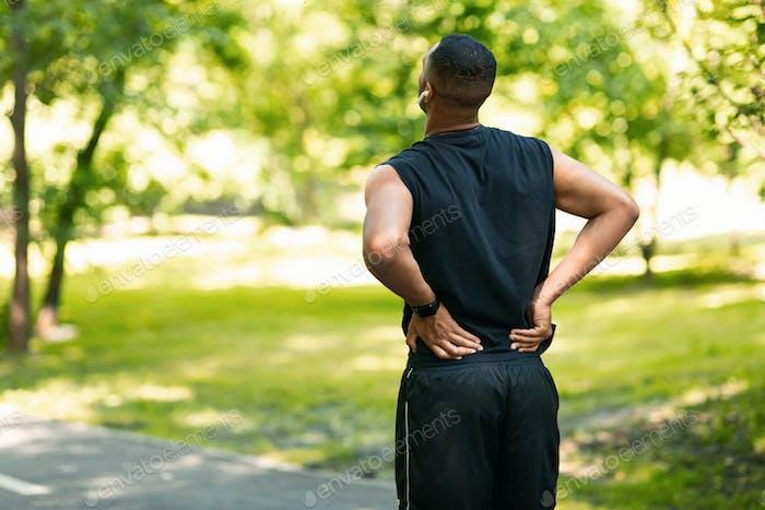 Millennial guy in sportswear suffering from back pain wgilejogging at park, empty space