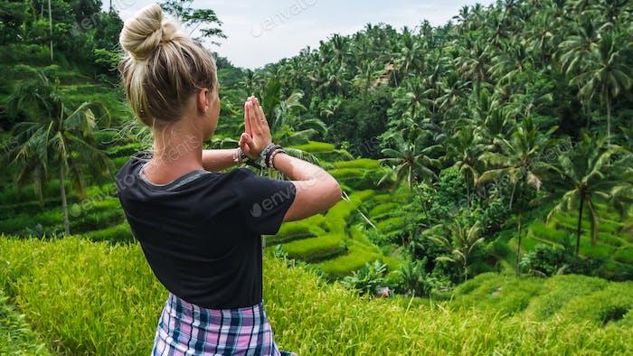 Female meditating on Tegalalang Rice Terrace, Ubud, Bali, Indonesia