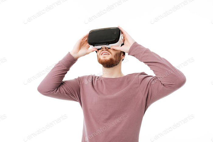 Young boy playing with visual reality glasses over white background