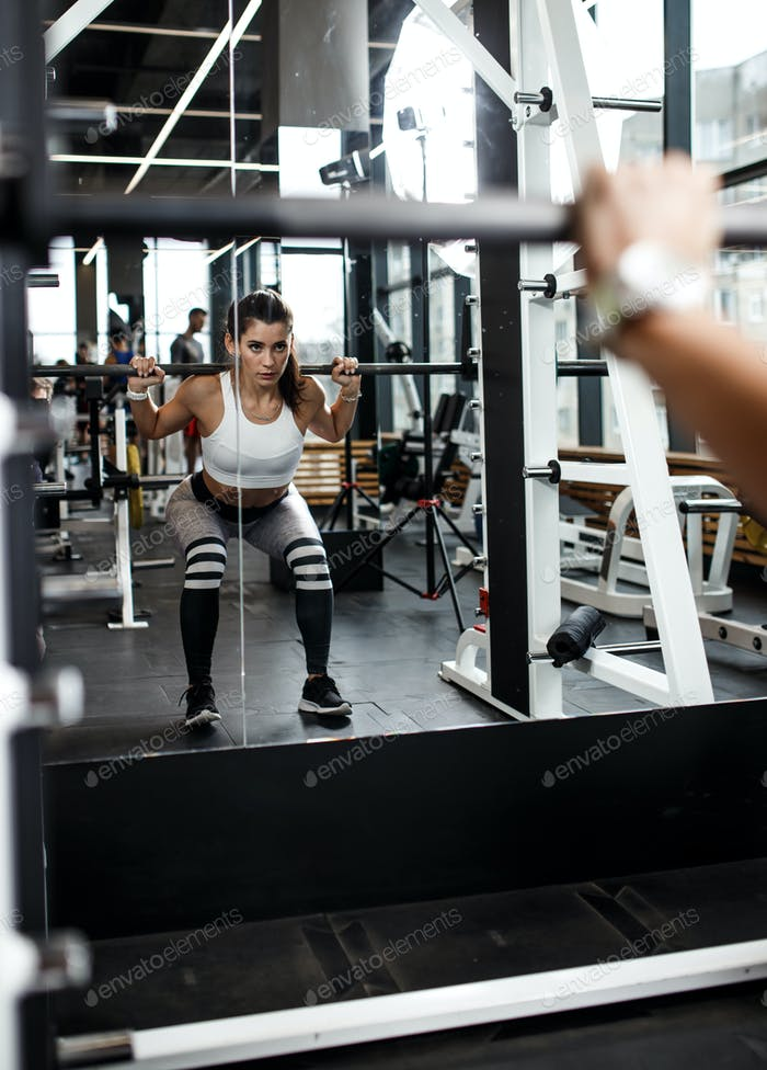 Young athletic girl dressed in sportswear squats with a barbell in front of the mirror in the modern