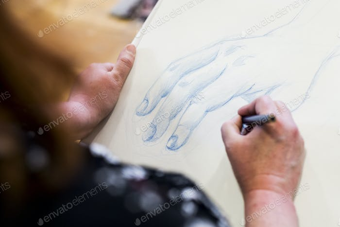 High angle close up of artist drawing human hand.