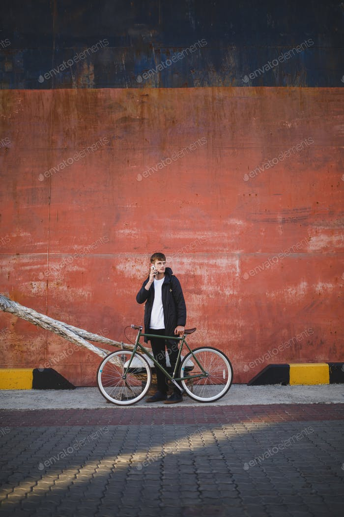 Cool boy with brown hair standing with bicycle and looking aside while talking on his cellphone