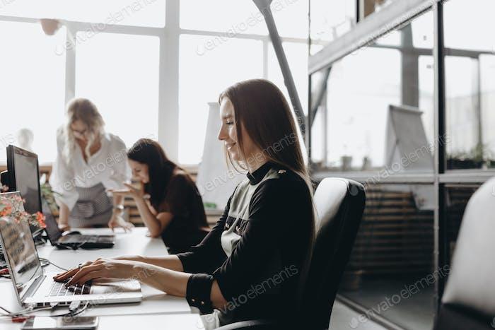 Junge schöne Frauen gekleidet nach Büro dreskod arbeiten an den Schreibtischen mit einem Computer