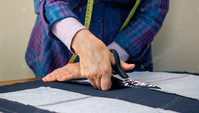 Hands of dressmaker cutting a cloth