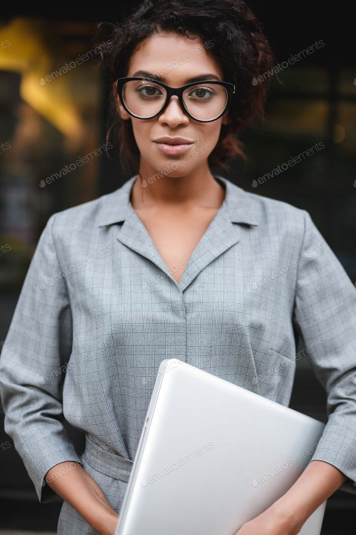 Young lady with dark curly hair in gray dress standing with laptop on street