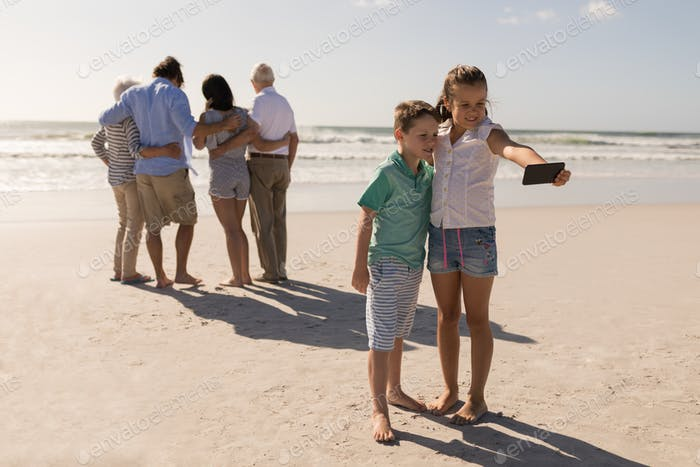 Siblings taking selfie with mobile phone while their family standing in background on beach