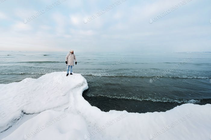 A tourist stands on the shore of the Baltic sea in winter. Winter near the Baltic States of Tallinn