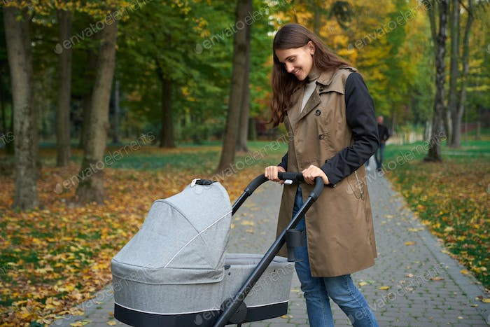 Woman in grey coat standing with baby stroller